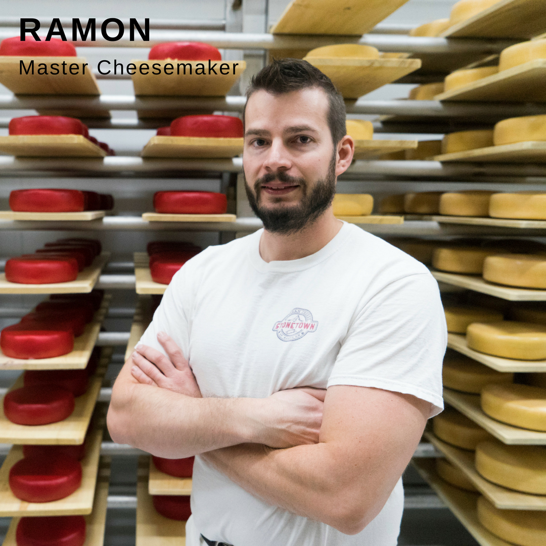 Man smiling while standing in front of wheels of cheese